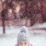 Little Girl Playing in the Winter Snow